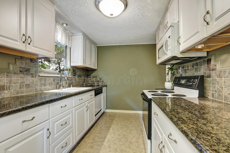 Interior of kitchen room with white cabinets, granite tops. Natural stone back splash tile trim and linoleum floor. Northwest, USA royalty free stock images