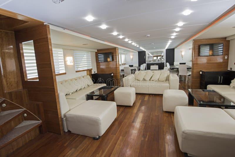 Interior of large salon area of luxury motor yacht. Interior design furnishing decor of the salon area in a large luxury motor yacht royalty free stock images