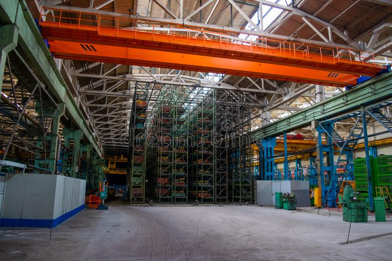 The interior of a large warehouse of heavy iron products and metal goods with pallet storage shelves at a production forge plant. Rows of shelves in commercial royalty free stock photo