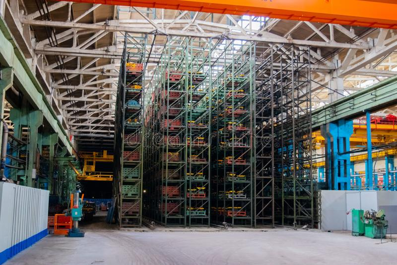 The interior of a large warehouse of heavy iron products and metal goods with pallet storage shelves at a production forge plant. Rows of shelves in commercial stock photography