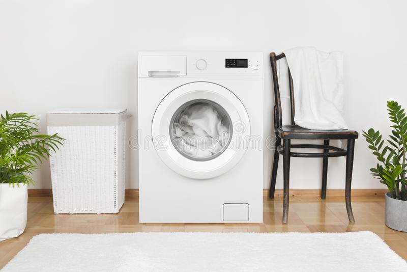 Interior of laundry room with washing machine and laundry basket royalty free stock images