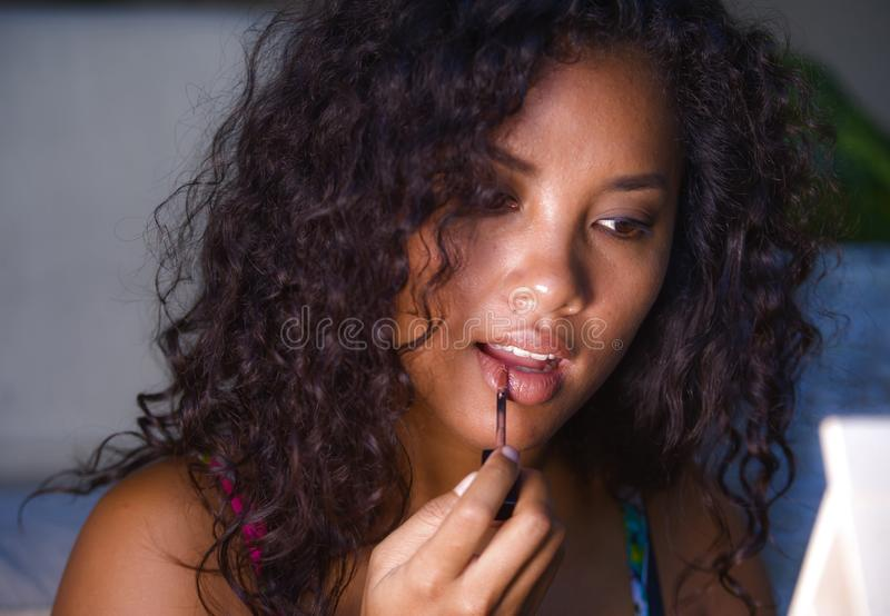 Portrait of young beautiful and natural mixed ethnicity Caucasian and afro American woman using makeup on her lips at home in stock photo