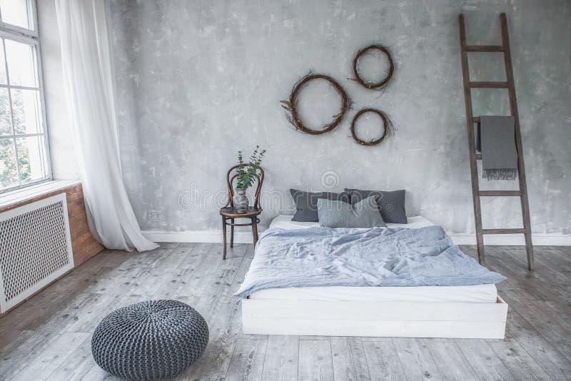 Interior ligero del dormitorio del estilo del desván, diseño hecho en los colores grises y púrpuras con muebles modernos, ventana imagen de archivo libre de regalías