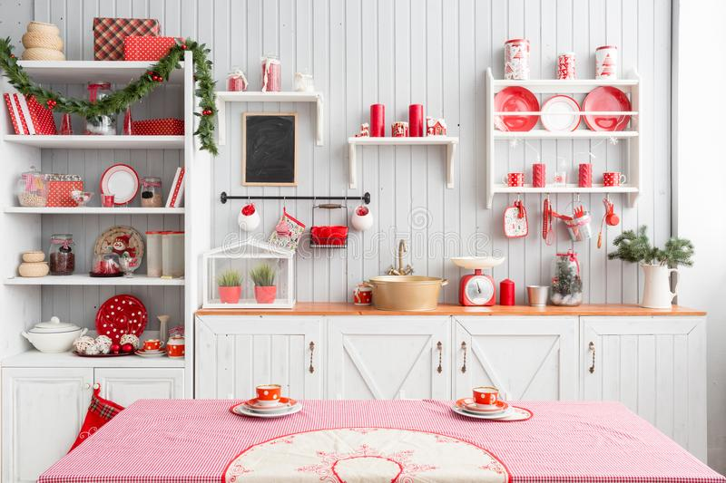 Interior light grey kitchen and red christmas decor. Preparing lunch at home on the kitchen concept. Interior light grey kitchen and red christmas decor royalty free stock photo