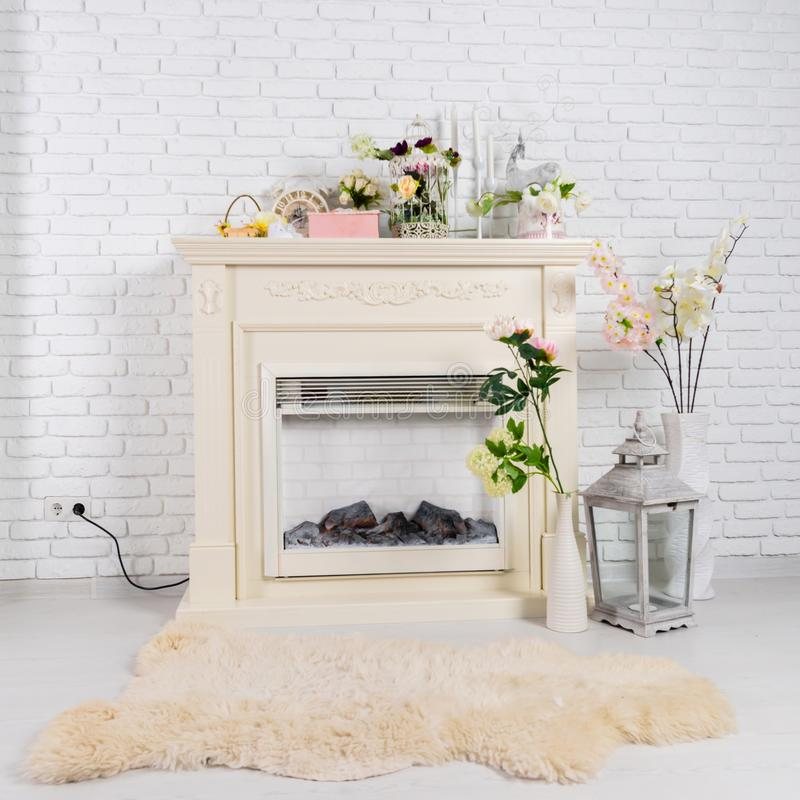 Interior in a light living room with fireplace, flowers and soft stock photos