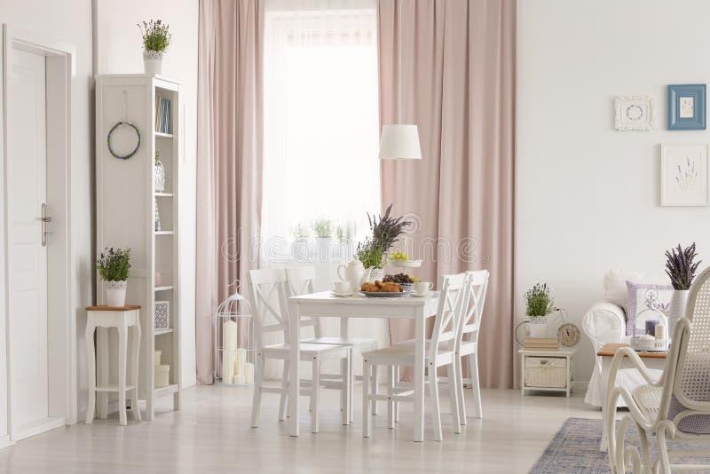Interior liso branco com a janela com cortinas, alfazema fresca, mesa de jantar com café da manhã e cartazes na parede na foto re foto de stock royalty free