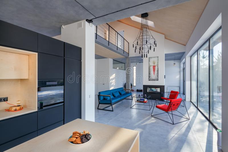 interior of the living room with kitchen; fireplace and panoramic windows royalty free stock photography