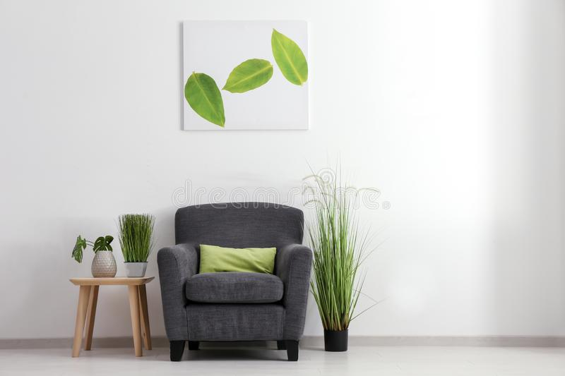 Interior of living room with stylish comfortable armchair near light wall royalty free stock photos