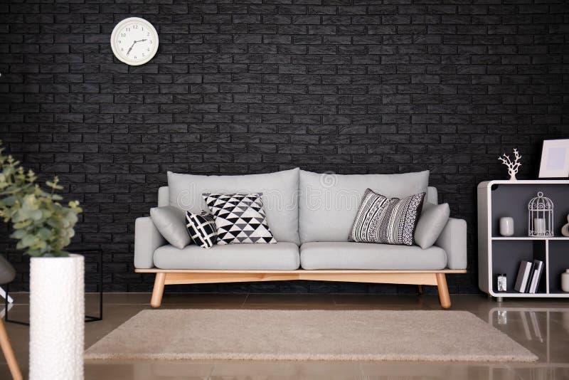 Interior of living room with stylish comfortable sofa near black brick wall royalty free stock photography