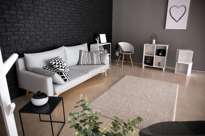 Interior of living room with stylish comfortable sofa near black brick wall stock image