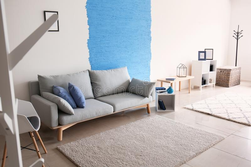 Interior of living room with stylish comfortable sofa near colorful wall stock photos