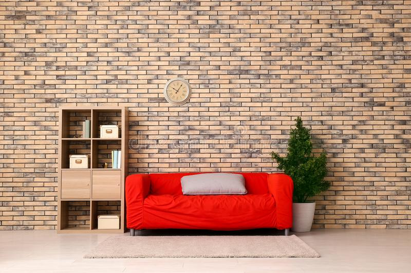Interior of living room with stylish red sofa near brick wall royalty free stock photo