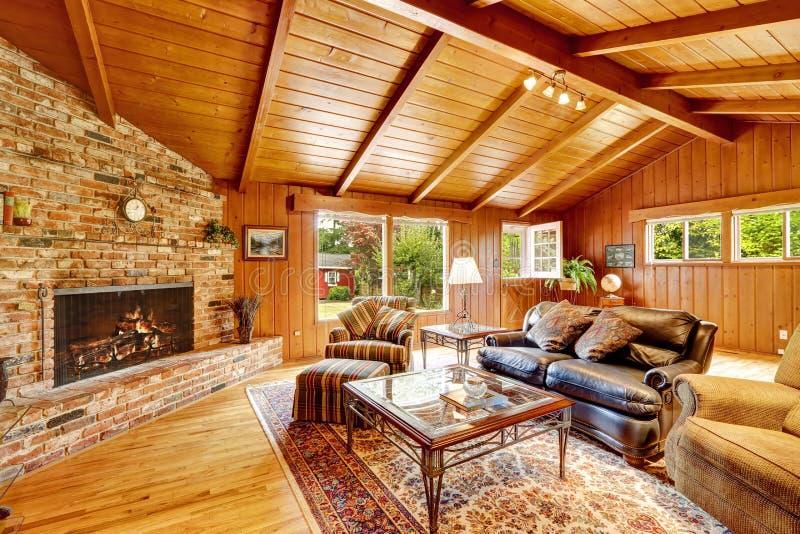 Interior luxuoso da casa da cabana rústica de madeira Sala de visitas com chaminé e imagens de stock royalty free