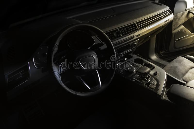 Interior of luxury suv car with black leather steering wheel and shift gear. Alcantara cockpit seats and doors. Black dashboard royalty free stock images