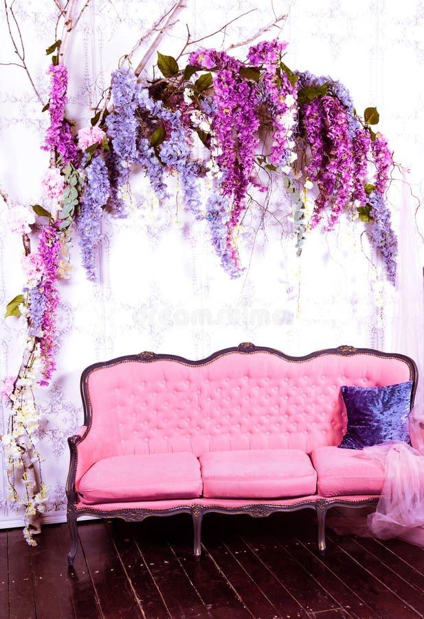 Interior magnífico adornado pared blanca púrpura azul vieja de la guirnalda de la flor del rosa del sofá imágenes de archivo libres de regalías