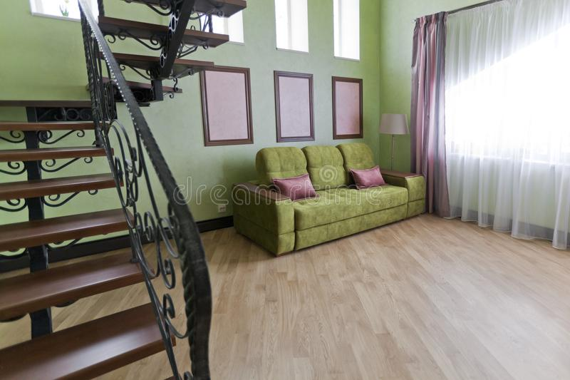 Interior with a metallic black staircase with wooden steps and a green sofa in the living room stock images