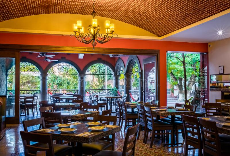 Interior mexicano tradicional do restaurante com cadeiras e teto das tabelas, do candelabro e do tijolo imagem de stock royalty free