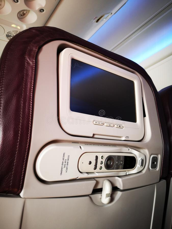 Closeup interior of mini television on flight for passengers on seats inside airplanes view. stock photo