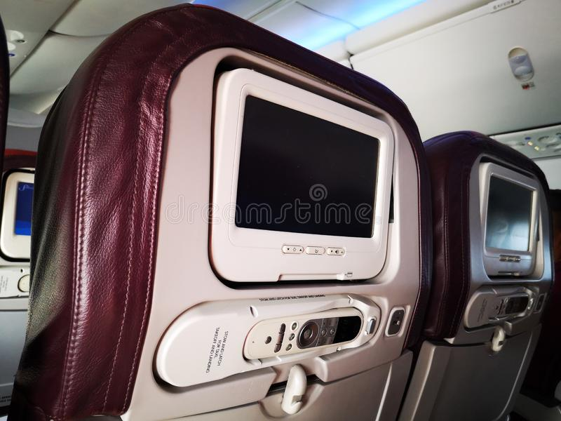 Closeup interior of mini television on flight for passengers on seats inside airplanes view. royalty free stock images