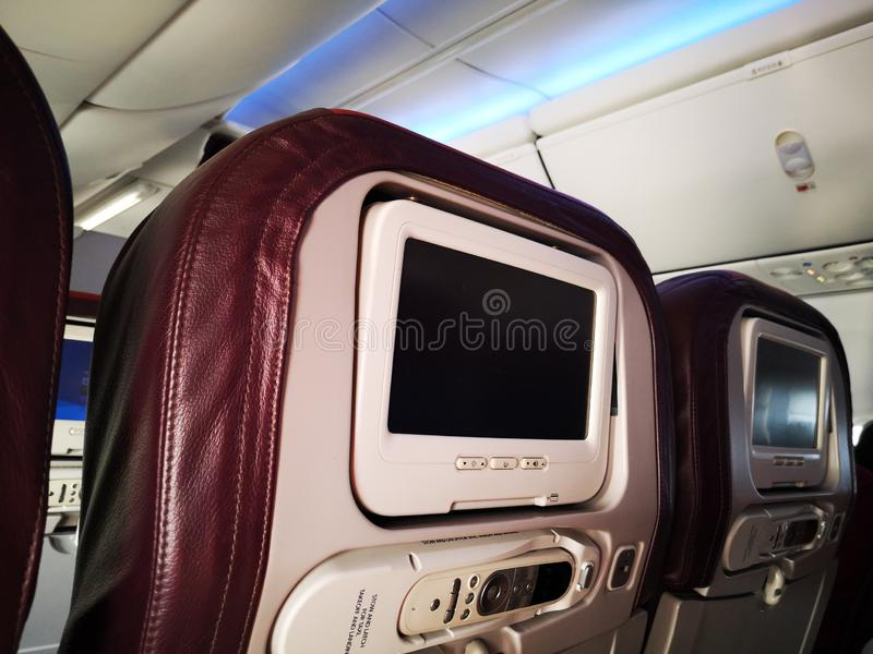 Closeup interior of mini television on flight for passengers on seats inside airplanes view. royalty free stock photos