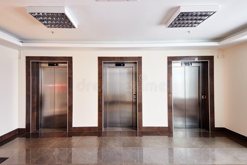 Interior minimalista moderno da entrada do centro de negócio com as três portas de aço fechados do elevador fotos de stock