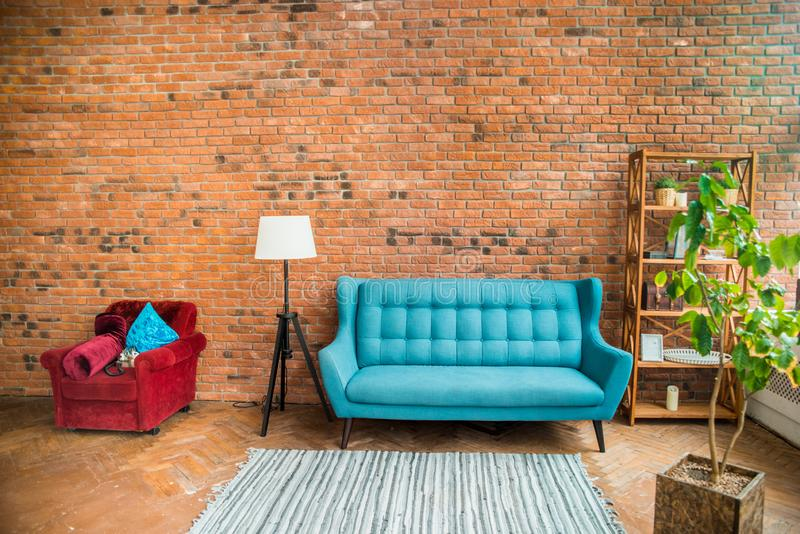 Interior mock up photo. Brownish brick wall with leather sofa and pot with plant. Background photo with copy space for text. Red chair and blue sofa. Textured stock images