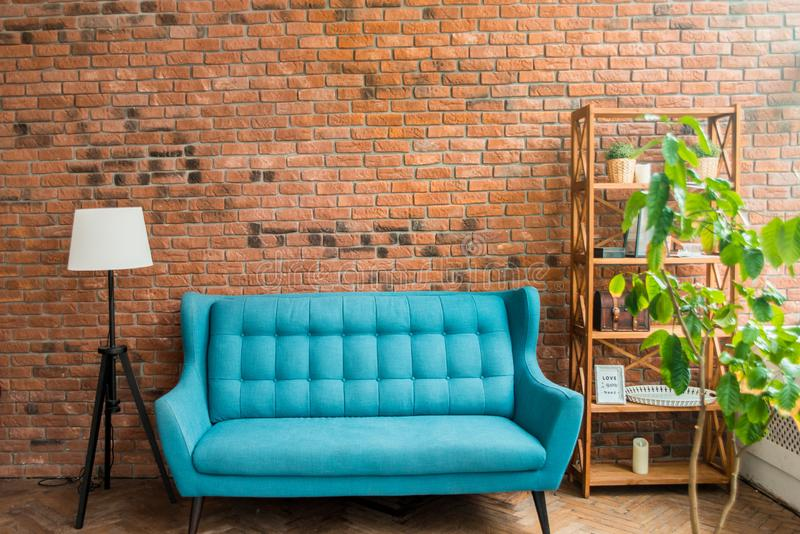 Interior mock up photo. Brownish brick wall with leather sofa and pot with plant. Background photo with copy space for text. Red chair and blue sofa. Textured royalty free stock photography