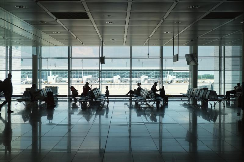 Interior of modern airport with silhouettes of passengers royalty free stock images
