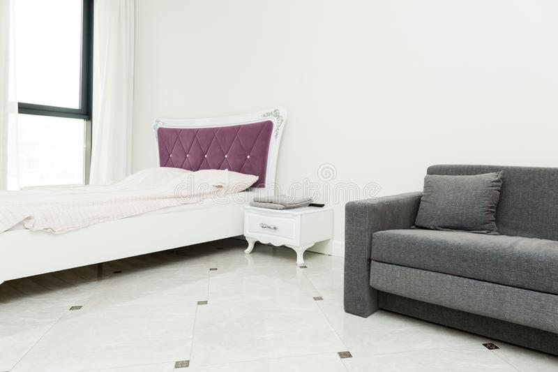 The interior of a modern apartment in a bright Scandinavian style with a color accent, a sofa and a bed stock photos