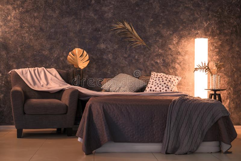 Interior of modern comfortable bedroom with golden tropical leaves stock photos