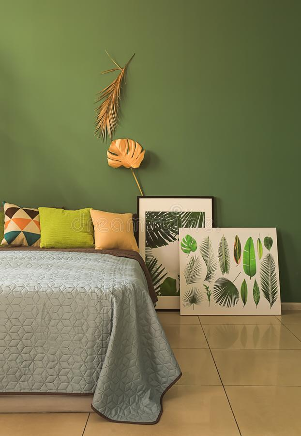 Interior of modern comfortable bedroom with golden tropical leaves on color wall royalty free stock photography