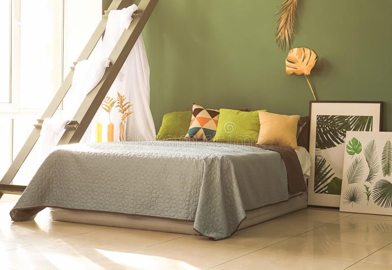 Interior of modern comfortable bedroom with golden tropical leaves on color wall stock photo