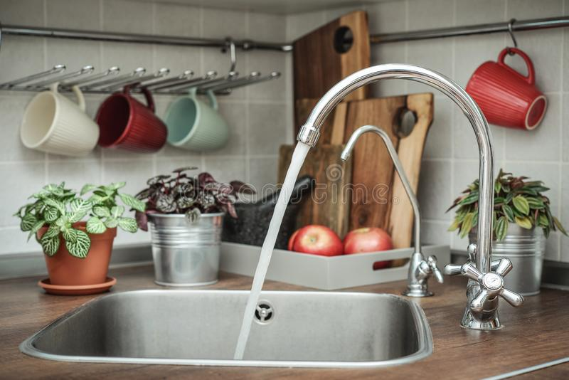 Domestic kitchen with water faucet. Interior of a modern domestic kitchen with water faucet closeup royalty free stock image