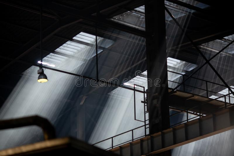 Interior of modern industrial production plant in beams of luminous lights royalty free stock photo