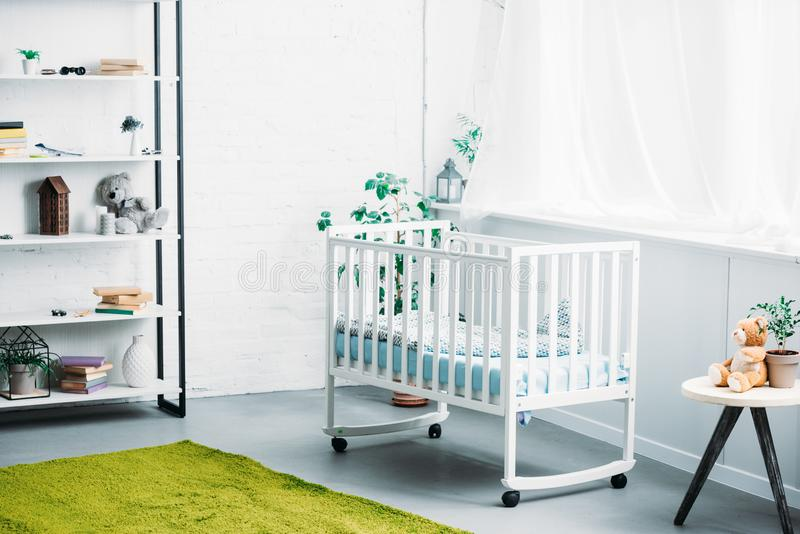 Interior of modern light childrens room with crib royalty free stock image