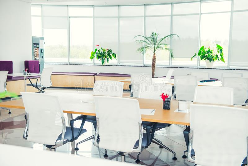 Interior of modern light empty open space office with big windows, table desks, chairs and green plants. Coworking workplace conce royalty free stock photography