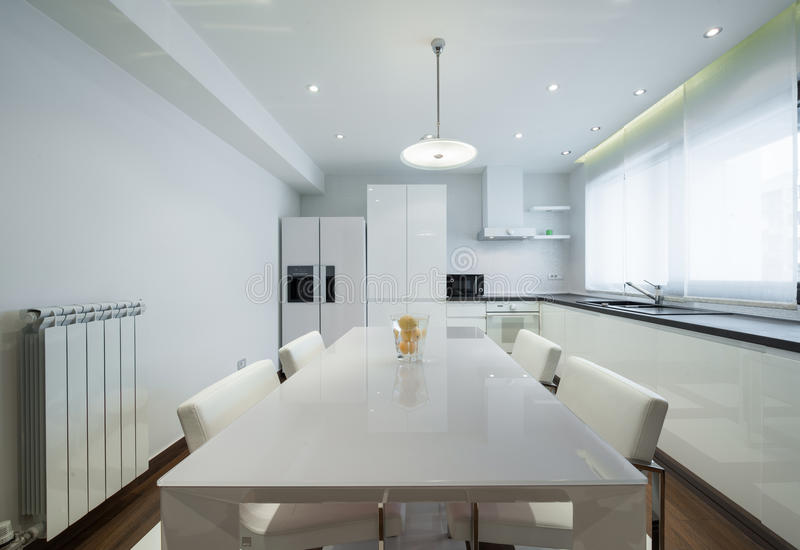 Interior of a modern luxury bright white kitchen with dining tab. Le stock photo