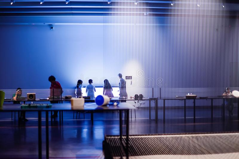 The interior of the modern museum or gallery with silhouettes of people and objects of the exhibition. Selective focus. royalty free stock image