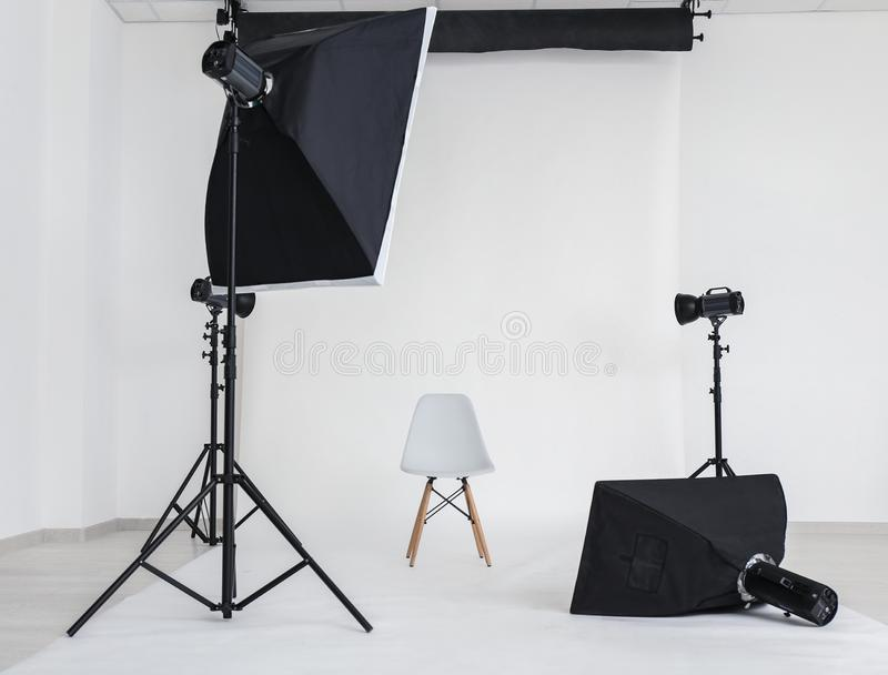 Interior of modern photo studio with chair and professional equipment royalty free stock photo