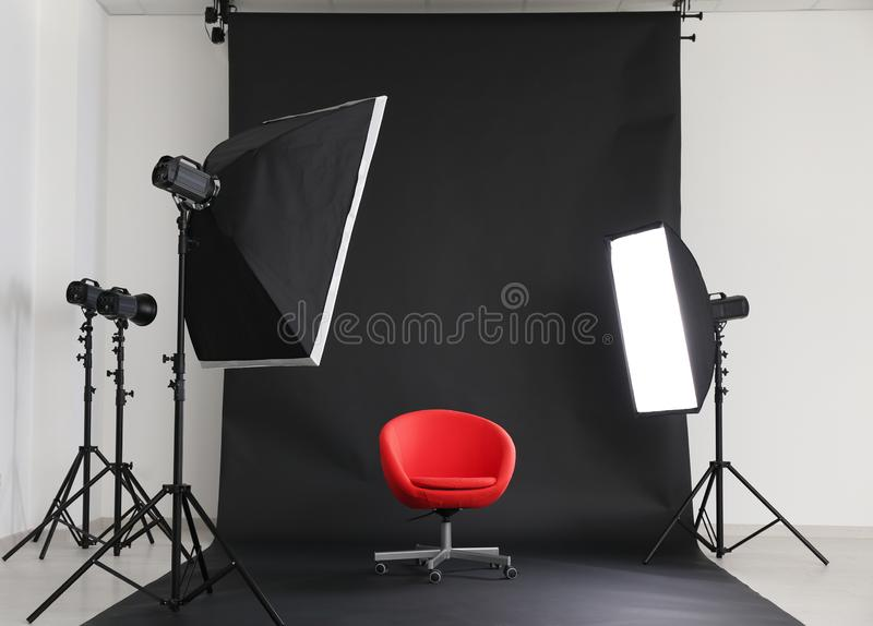 Interior of modern photo studio with chair and professional equipment royalty free stock photography