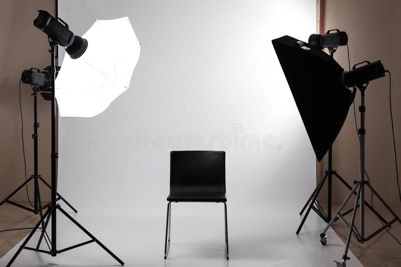 Interior of modern photo studio with professional equipment and chair royalty free stock images
