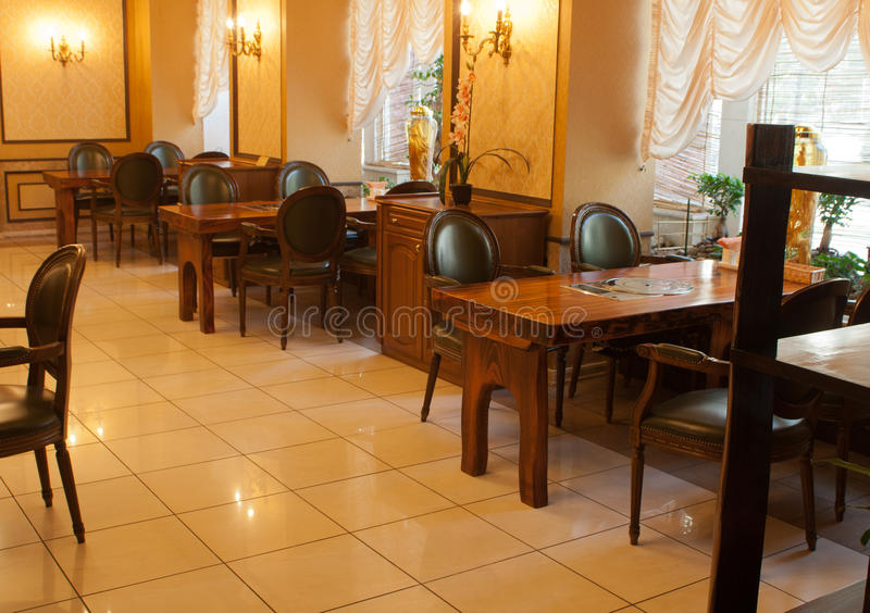Interior of modern restaurant. With wooden tables and chairs royalty free stock photos
