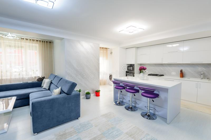 Interior of modern white studio apartment with kitchen. Interior of modern studio apartment with white kitchen and sofa, purple bar chairs, minimalistic clean stock photos