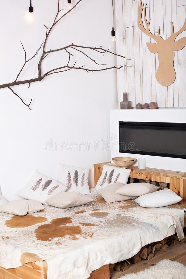 Interior of a modern wooden bedroom in country style rustic. bed with pillows near the electric fireplace. Cozy Christmas home i royalty free stock image