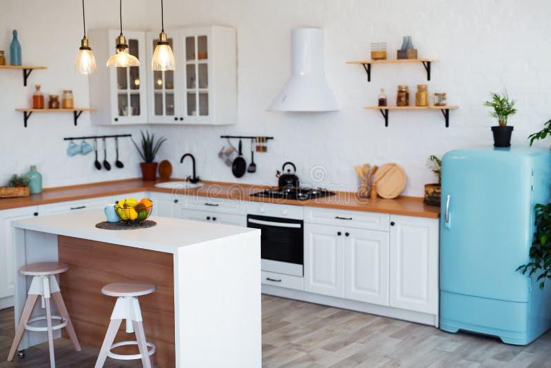Interior moderno da cozinha com ilha, dissipador, armários, e a janela grande na casa luxuosa nova imagem de stock royalty free