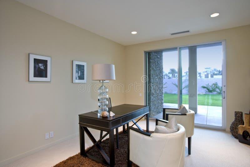 Interior moderno de la casa con el escritorio y las sillas fotos de archivo