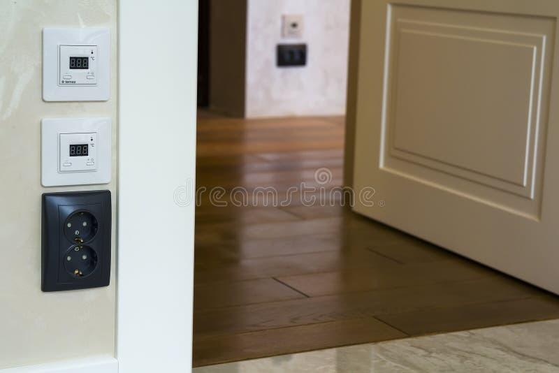 Interior moderno de la casa con los paneles calientes del regulador del piso en la pared, el entarimado de madera y la puerta bla foto de archivo libre de regalías