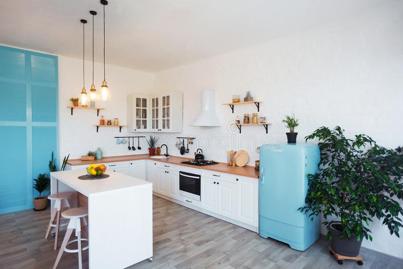Interior moderno de la cocina con la isla, el fregadero, los gabinetes, y la ventana grande en nuevo hogar de lujo fotos de archivo