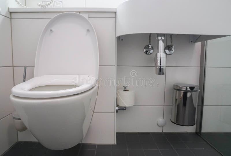 Interior moderno del cuarto de baño del fregadero de cerámica blanco de la taza del inodoro y del lavabo con el compartimiento in fotografía de archivo libre de regalías