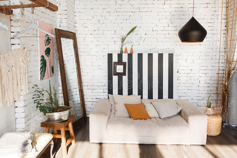 Interior moderno del desván con el sofá, la lámpara del estudio, el espejo, las rayas en la pared de ladrillo blanca y las flores fotos de archivo